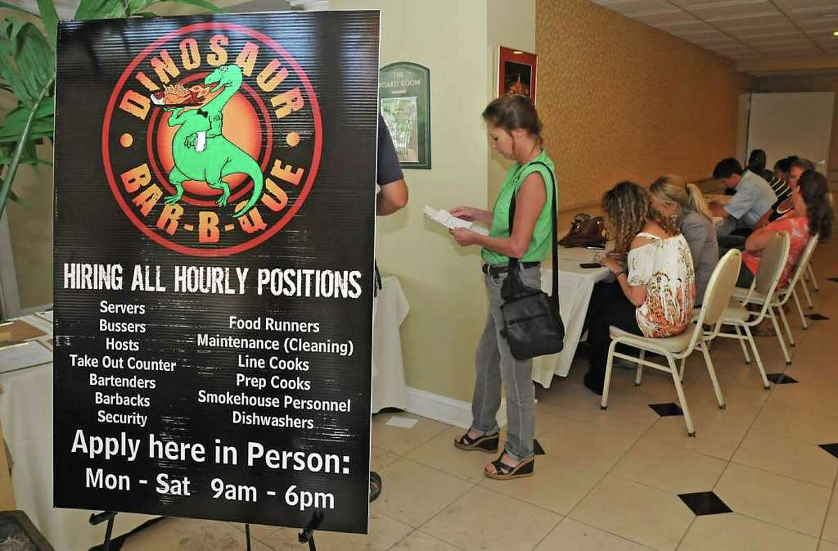 Applicants fill out applications in the lobby of the Best Western Franklin Square Inn for jobs at Dinosaur Bar-B-Que. (Lori Van Buren / Times Union)