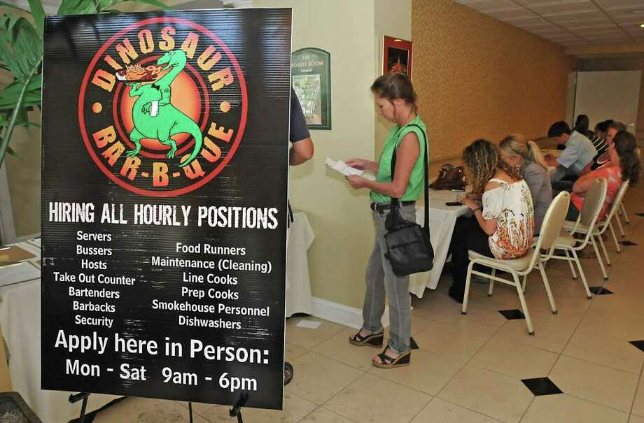 Applicants fill out applications in the lobby of the Best Western Franklin Square Inn for jobs at Dinosaur Bar-B-Que. (Lori Van Buren / Times Union) Photo: Lori Van Buren