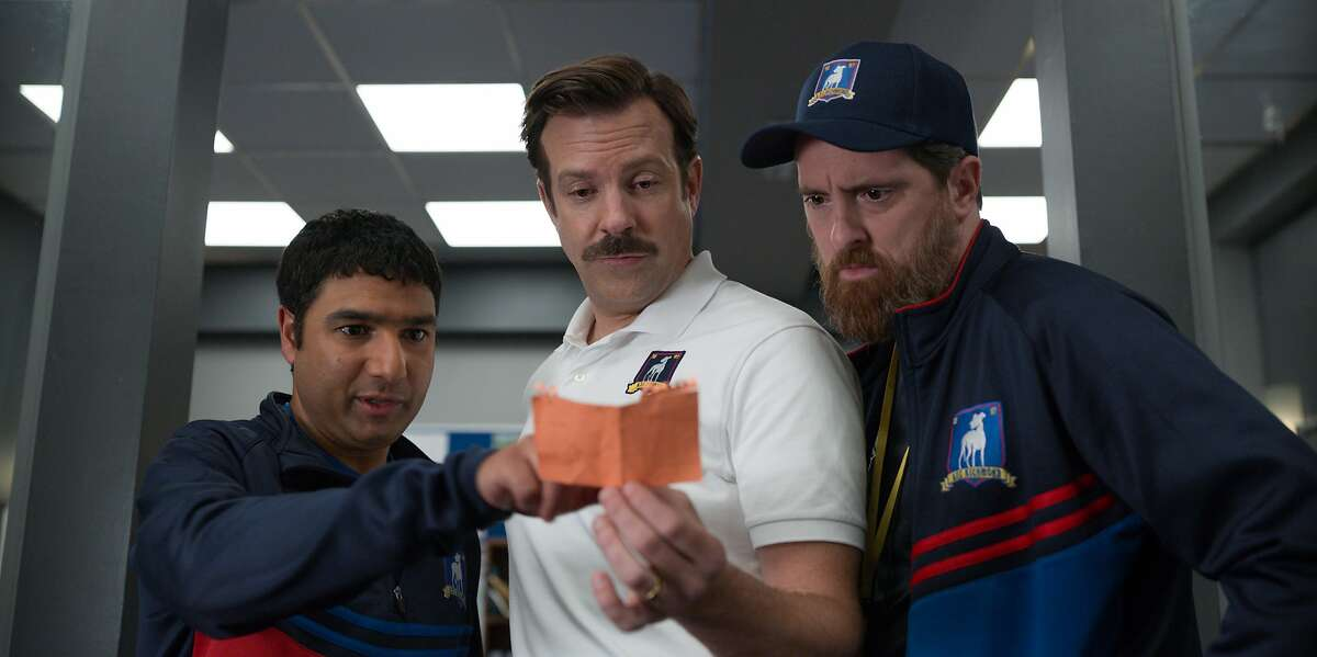 """This image released by Apple TV Plus shows Nick Mohammed, from left, Jason Sudeikis, and Brendan Hunt in """"Ted Lasso."""" The show could have a field day incorporating the rise and immediate fall of the Super League into its storyline."""