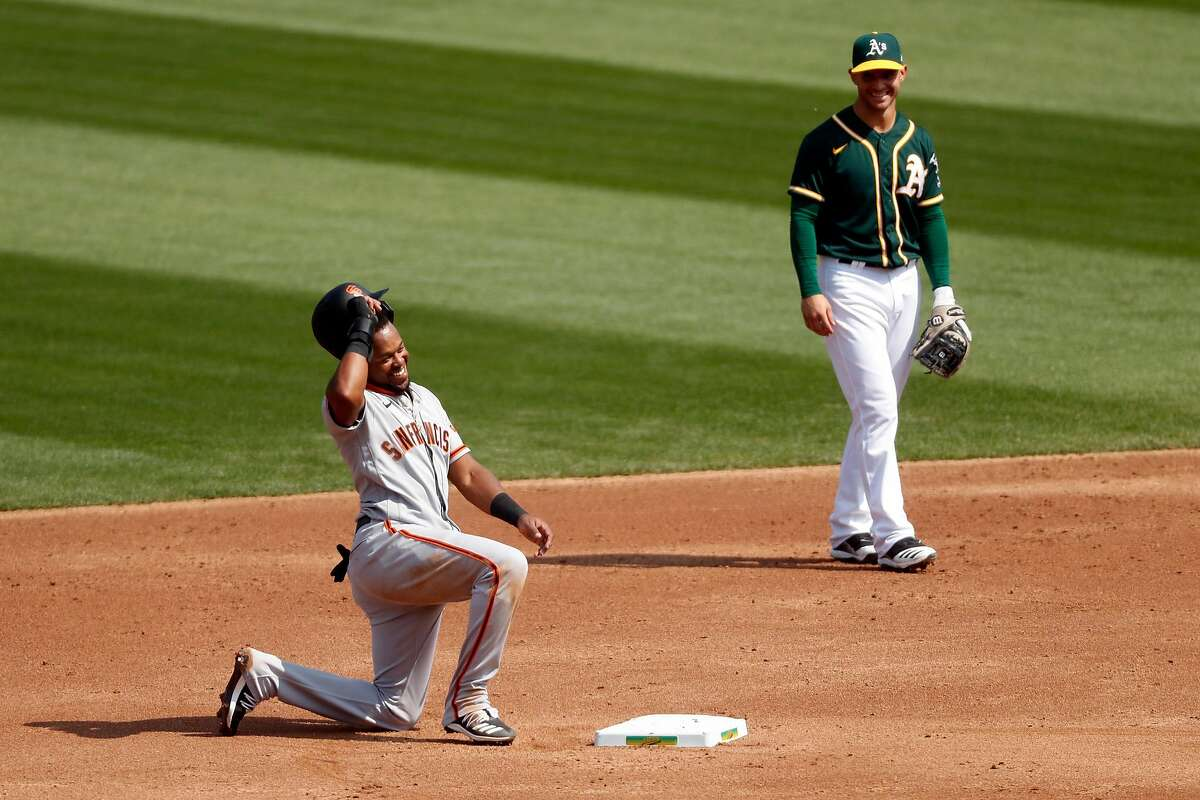 San Francisco Giants' Luis Basabe and Oakland Athletics' Tommy La Stella smile after Basabe slid back into second base on a fake pick off play in 3rd inning in MLB game at Oakland Coliseum in Oakland, Calif., on Sunday, September 20, 2020.