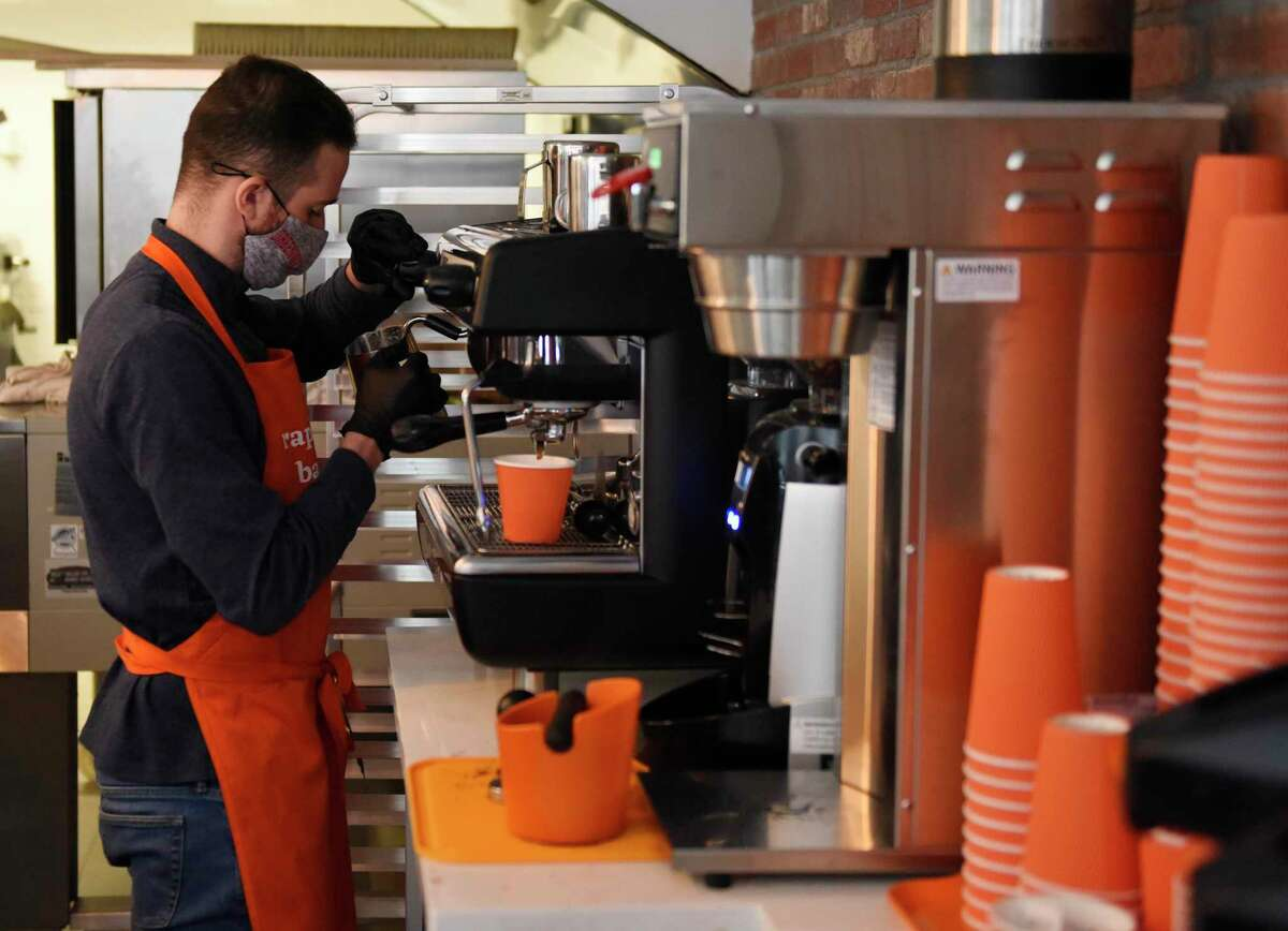 Kelian Dequeker makes an espresso drink at the opening of Raphaël's Bakery in Greenwich, Conn. Sunday, Dec. 20, 2020. Located at 146 Mason St., the French Bakery features fine bread, patisserie, and espresso from the former head pastry chef at Valbella in Riverside.
