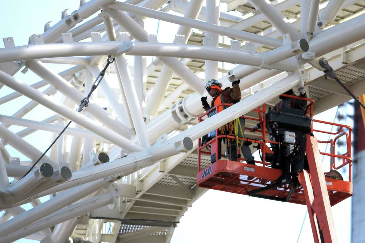 Worker guide a section of metal framing into place above the Harbor Yard Amphitheater currently under construction in Bridgeport, Conn. Jan. 25, 2021. The framework will support the massive fabric tent roof that will soon cover the amphitheater.