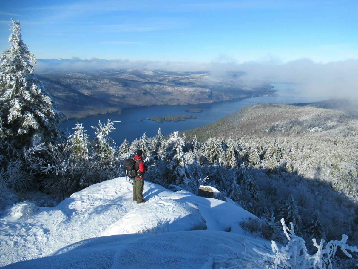 A hiker looks out over Lake George from the summit of Black Mountain in January.