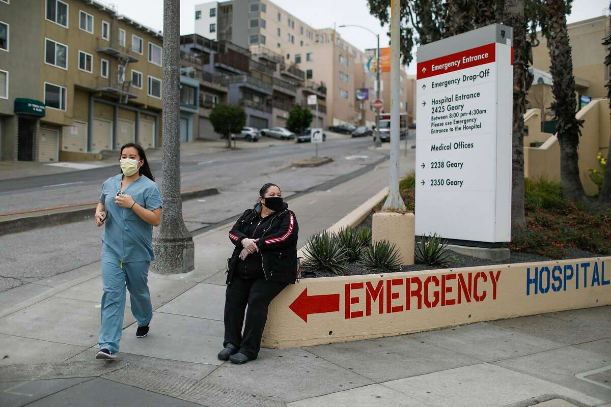 A nurse jogs past Angelica Rodriguez outside of Kaiser's emergency entrance in San Francisco.