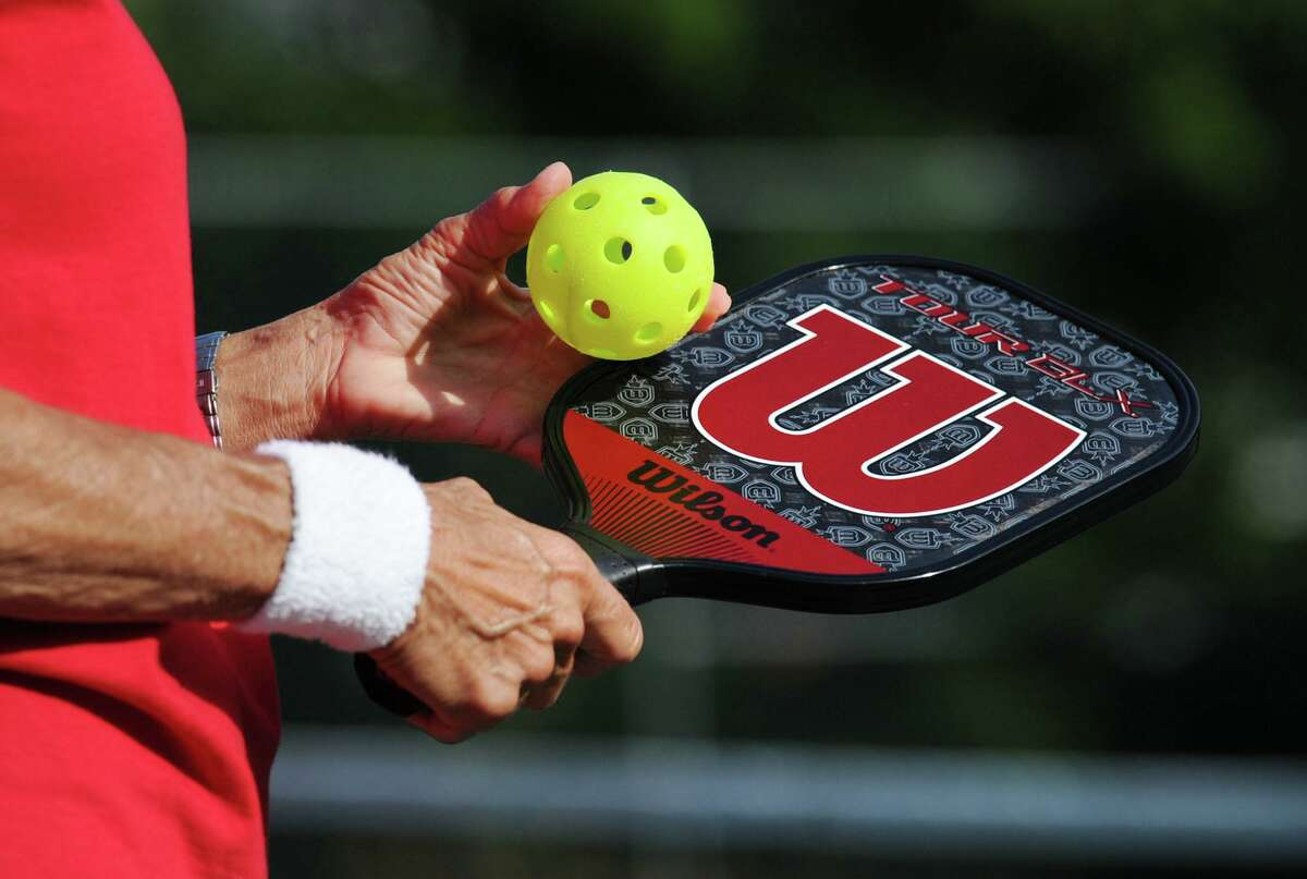 A player shows the paddle and ball used in Pickleball.