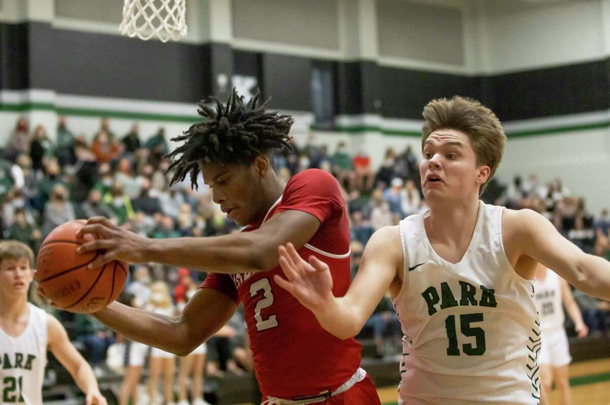 Cleveland guard Devonate Robertson (2) and Kingwood Park Jake Bayless (15) fight for control of a rebound during the third quarter of a 20-5A District basketball game at Kingwood Park High School, Wednesday, Feb. 10, 2021, in Kingwood.
