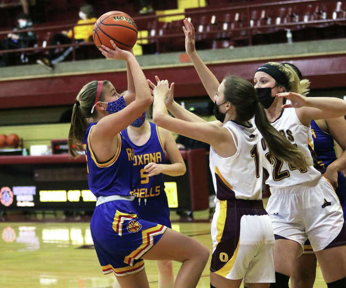 Roxana's Macie Lucas (left) pulls up to shoot over EA-WR's Kayla Henkhaus (1) and Mia Plumb (24) during a Shells win last Saturday at Memorial Gym in Wood River.
