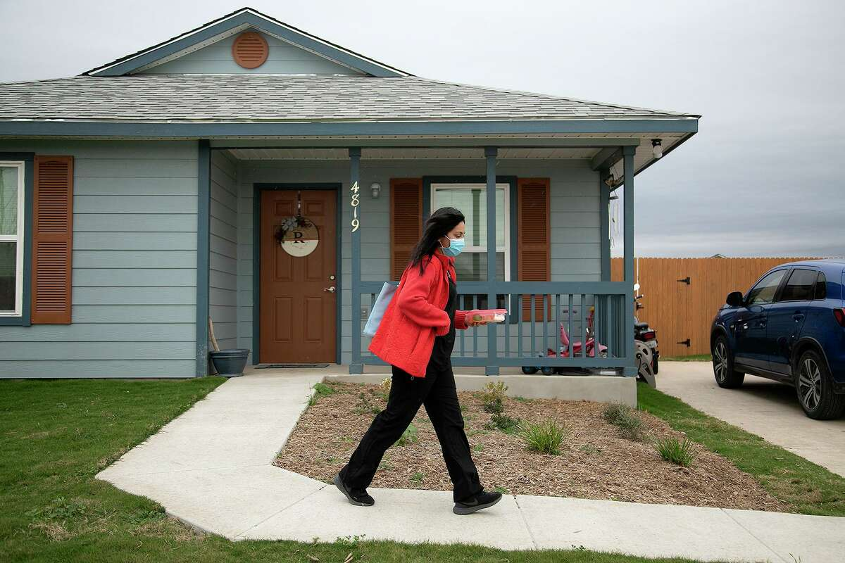 """Abigail Ruggiero heads to her job as a lab technician from her home in a Habitat For Humanity neighborhood in Von Ormy. Grants and """"sweat equity"""" helped make her dream a reality."""