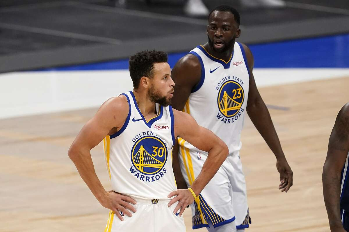 Golden State Warriors' Stephen Curry (30) celebrates with a dance move after sinking a three-point basket from near half court as Draymond Green (23) cheers him on in the second half of an NBA basketball game against the Dallas Mavericks in Dallas, Saturday, Feb. 6, 2021. (AP Photo/Tony Gutierrez)