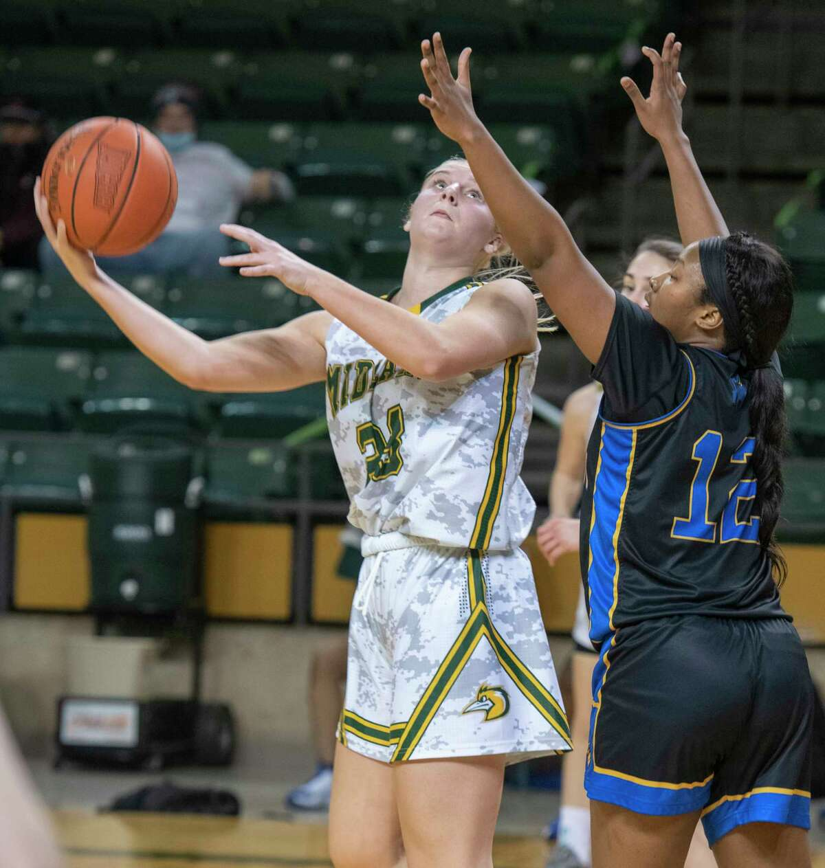 Midland College's Bella Green looks to make a hook shot as Frank Phillips' Alexys Grice defends 02/11/2021 at the Chaparral Center. Tim Fischer/Reporter-Telegram