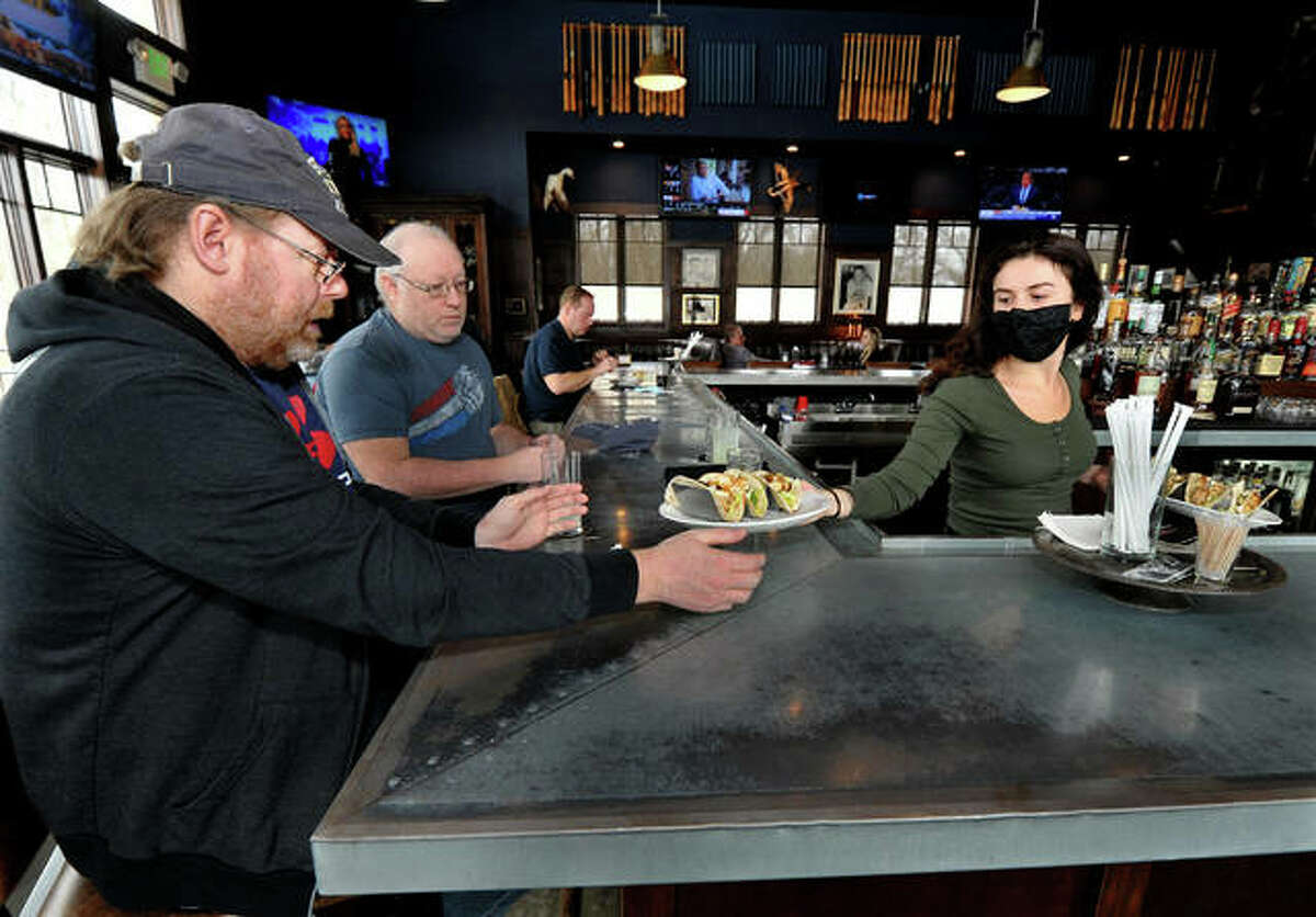 Christopher Peek of Collinsville, left, gets his lunch served to him by bartender Abby Martens, right, at Mike Shannon's Grill in Edwardsville Thursday. Mike Shannon's Grill in Edwardsville is running weeklong specials for Valentine's Day.