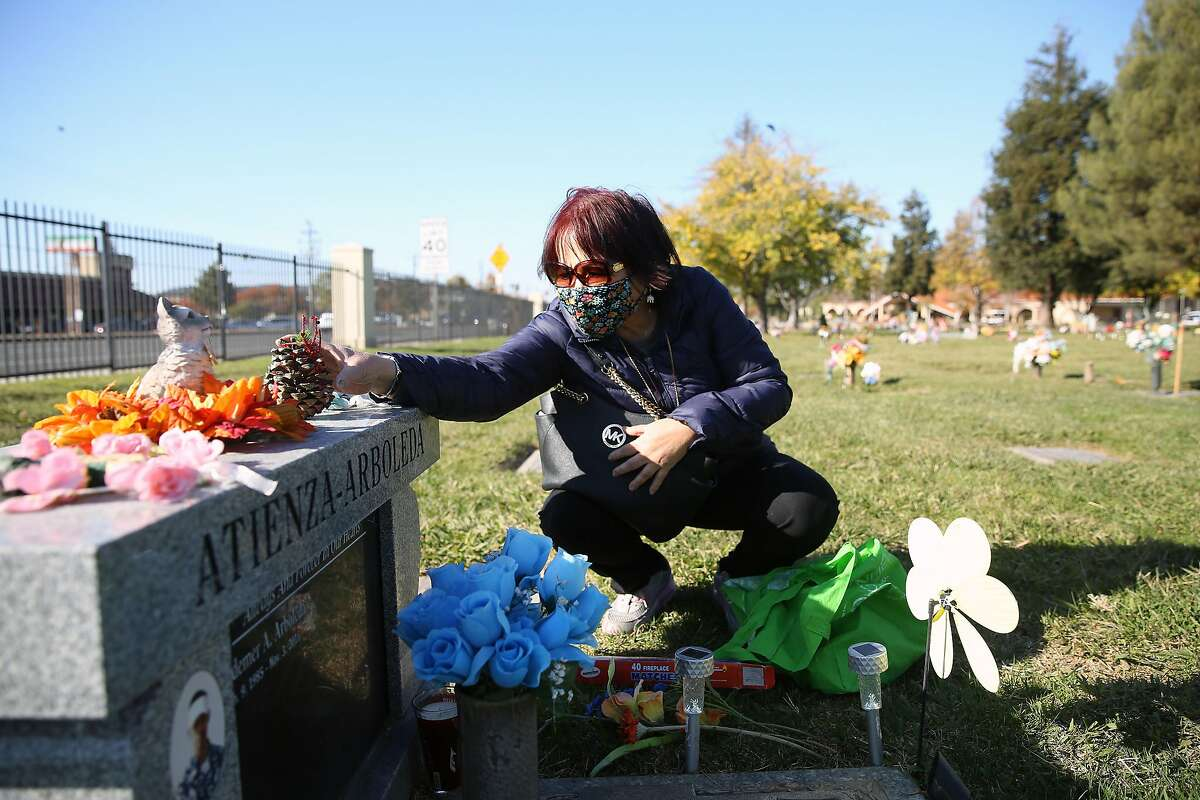 Jeannie Arboleda, mother of Laudemer Arboleda, decorates the headstone of her son Laudemer Arboleda with Christmas themed decorations during a visit to his grave site in the Sunrise Gardens at Chapel of the Chimes on Monday, November 30, 2020 in Hayward, Calif. Laudemer Arboleda was shot to death by a Danville police officer through the passenger window of his car while he was attempting to flee the police, unarmed and not accused of anything at the intersection of Diablo Road and Front Street in Danville, in 2018.