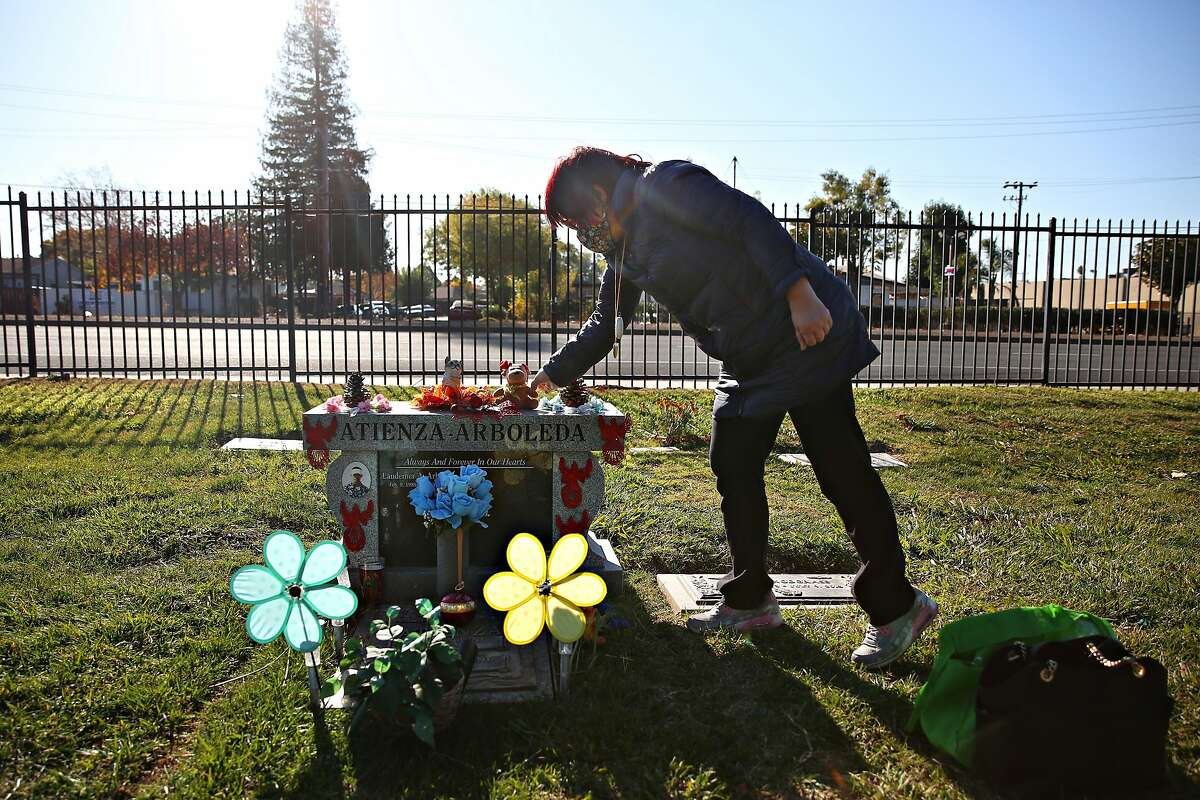 Jeannie Atienza decorates the headstone of her son Laudemer Arboleda, an unarmed motorist who was shot while attempting to flee Danville police.