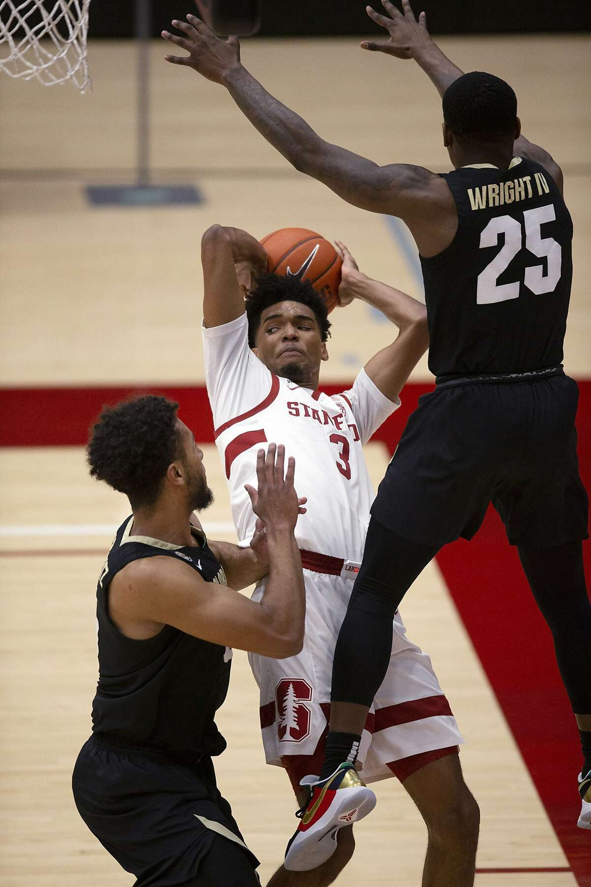 Stanford forward Ziaire Williams (3) looks to pass the ball as Colorado's D'Shawn Schwartz, left, and McKinley Wright IV (25) defend during the first half of an NCAA college basketball game Thursday, Feb. 11, 2021, in Stanford, Calif. (AP Photo/D. Ross Cameron)