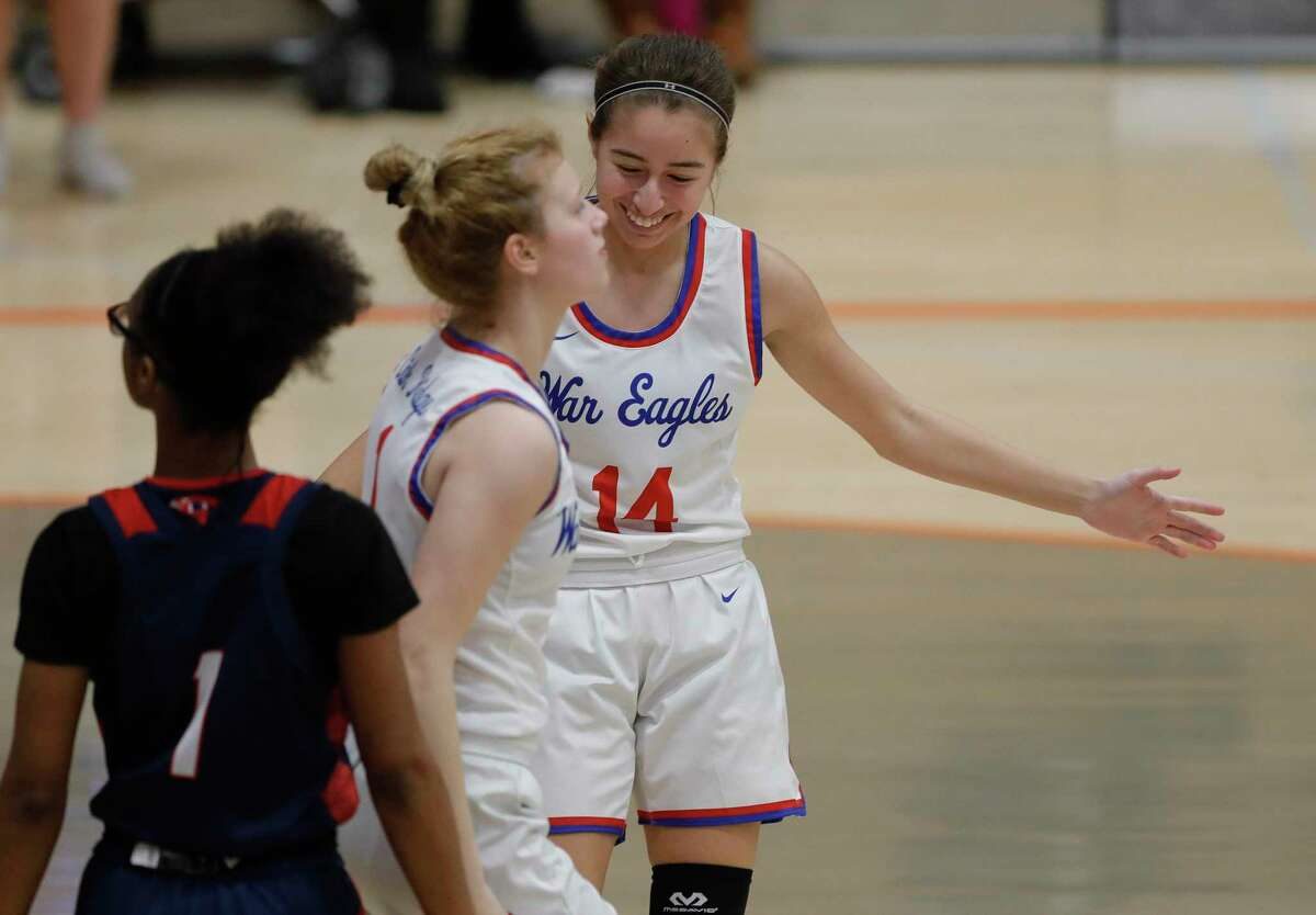 Oak Ridge's Kylie Weeks (14) gives Nikki Petrakovitz (1) a high-five after drawing a foul during the third quarter of a Region II-6A bi-district high school basketball playoff game at Grand Oaks High School, Thursday, Feb. 11, 2021, in Spring.