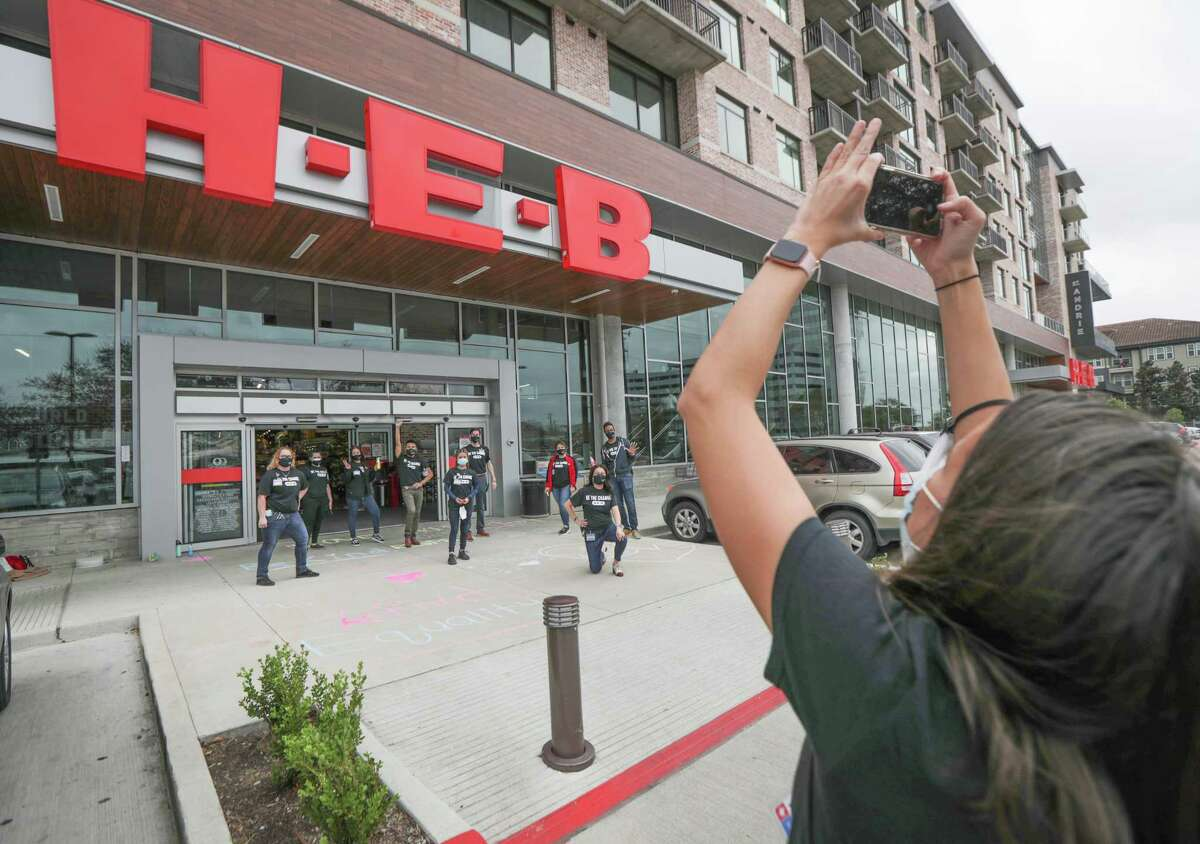Kate Gilbert takes a photo of team members in front of the H-E-B Buffalo Heights store, 3663 Washington, after they chalked positive messages in the entrance of the store. Beginning with Black History Month, H-E-B stores launched a new initiative called Be the Change, part of commitment to diversity and inclusion by spotlighting vendor brands owned by people of color, women, LGBTQ and people with disabilities within stores.