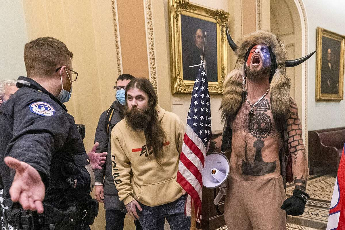 FILE - In this Wednesday, Jan. 6, 2021 file photo, supporters of President Donald Trump, including Jacob Chansley, right with fur hat, are confronted by U.S. Capitol Police officers outside the Senate Chamber inside the Capitol in Washington.