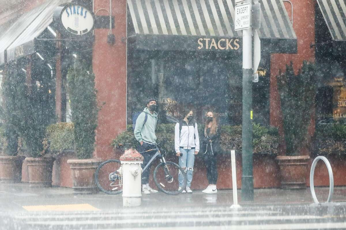 People take cover under an awning during a rainstorm in Hayes Valley on Thursday, Feb. 11, 2021 in San Francisco, California.