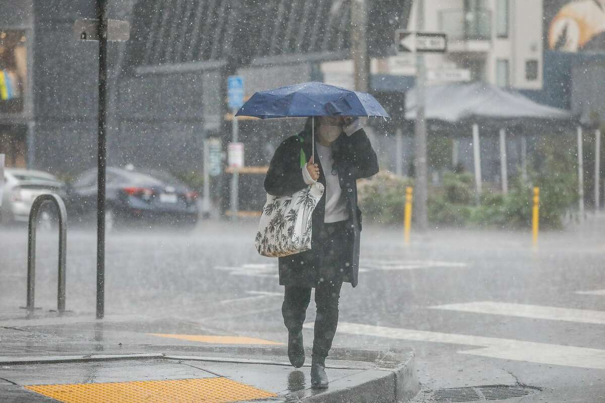 A woman walks through a rainstorm in Hayes Valley on Thursday, Feb. 11, 2021 in San Francisco, California.