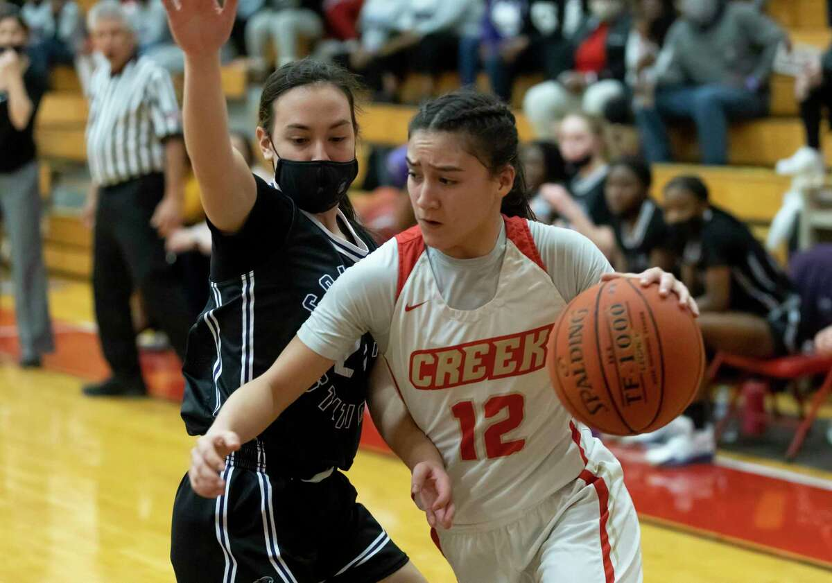 College Station guard Tanijah Richardson (12) drives the ball passed College Station forward Bianca Youlton (24) during the first quarter of a Region III-5A bi-district playoff game at Caney Creek High School, Thursday, Feb. 11, 2021, in Conroe.