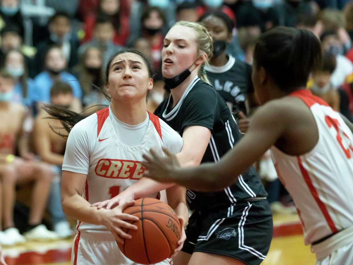 College Station guard Jaeden McMillin (32) blocks Caney Creek guard Olivia Hernandez (12) from shooting to the basket during the first quarter of a Region III-5A bi-district playoff game at Caney Creek High School, Thursday, Feb. 11, 2021, in Conroe.