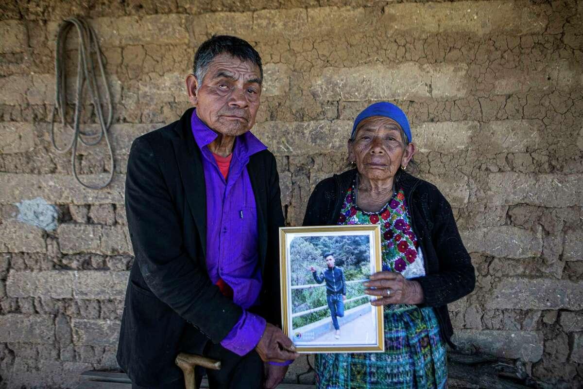 En esta fotografía de archivo del 27 de enero de 2021, Germán y María Tomasa posan en su casa en Comitancillo, Guatemala, con una fotografía de su nieto Iván Gudiel. Ambos dicen que uno de los cadáveres calcinados encontrados en un camino rural en la localidad mexicana de Camargo es el de su nieto