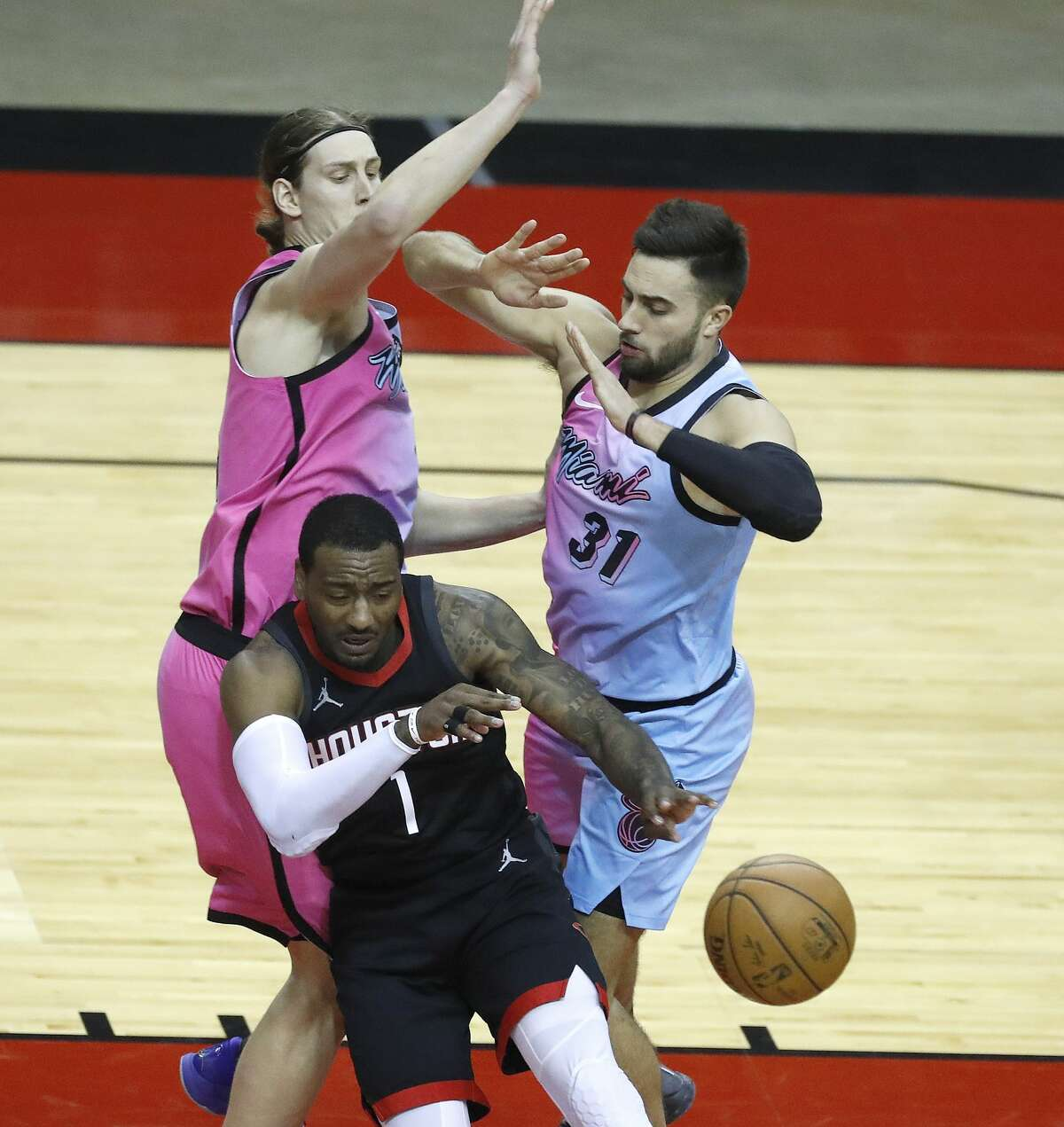Houston Rockets guard John Wall (1) loses control of the ball against Miami Heat forward Kelly Olynyk (9) and guard Max Strus (31) during the fourth quarter of an NBA basketball game at Toyota Center, in Houston, Thursday, February 11, 2021.