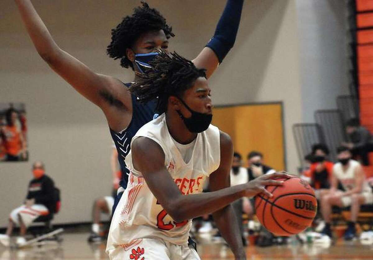 EHS guard Gabe James races down the court with a Belleville East defender on his hip in the second quarter of Thursday's game inside Lucco-Jackson Gymnasium in Edwardsville.