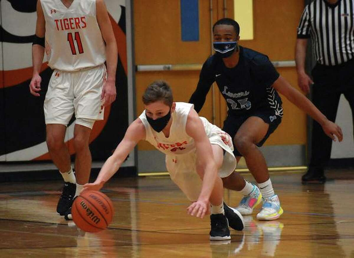 Edwardsville guard Preston Weaver dives for a loose ball at the end of the first quarter against Belleville East on Thursday in Edwardsville.