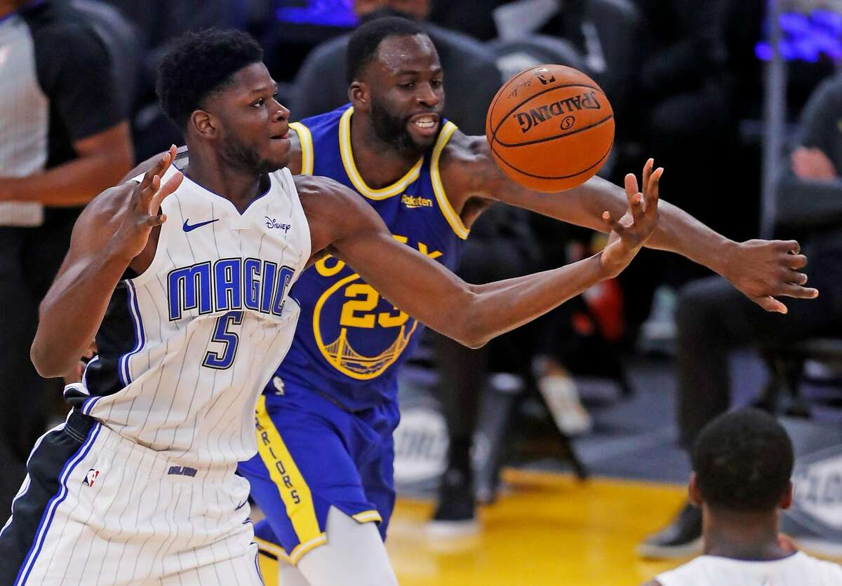 Golden State Warriors' Draymond Green and Orlando Magic's Mo Bamba vie for the ball in 2nd quarter during NBA game at Chase Center in San Francisco, Calif., on Thursday, February 11, 2021.