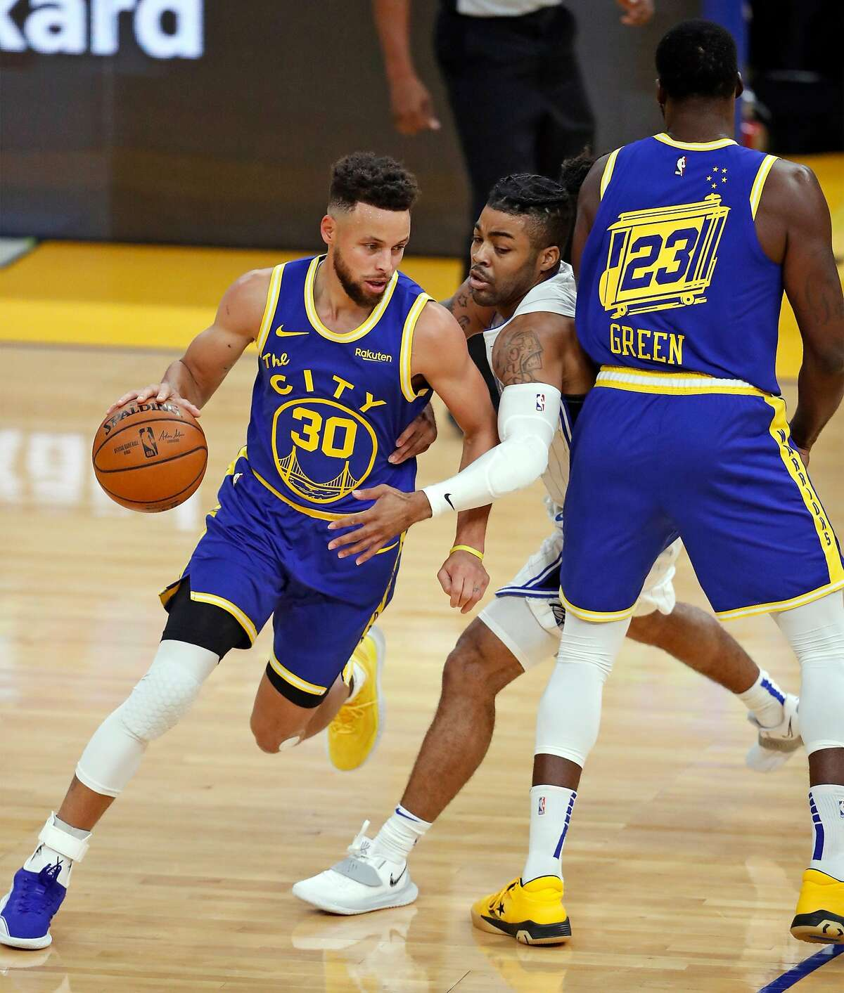 Golden State Warriors' Stephen Curry dribbles as Draymond Green screens Orlando Magic's Frank Mason III in 1st quarter during NBA game at Chase Center in San Francisco, Calif., on Thursday, February 11, 2021.