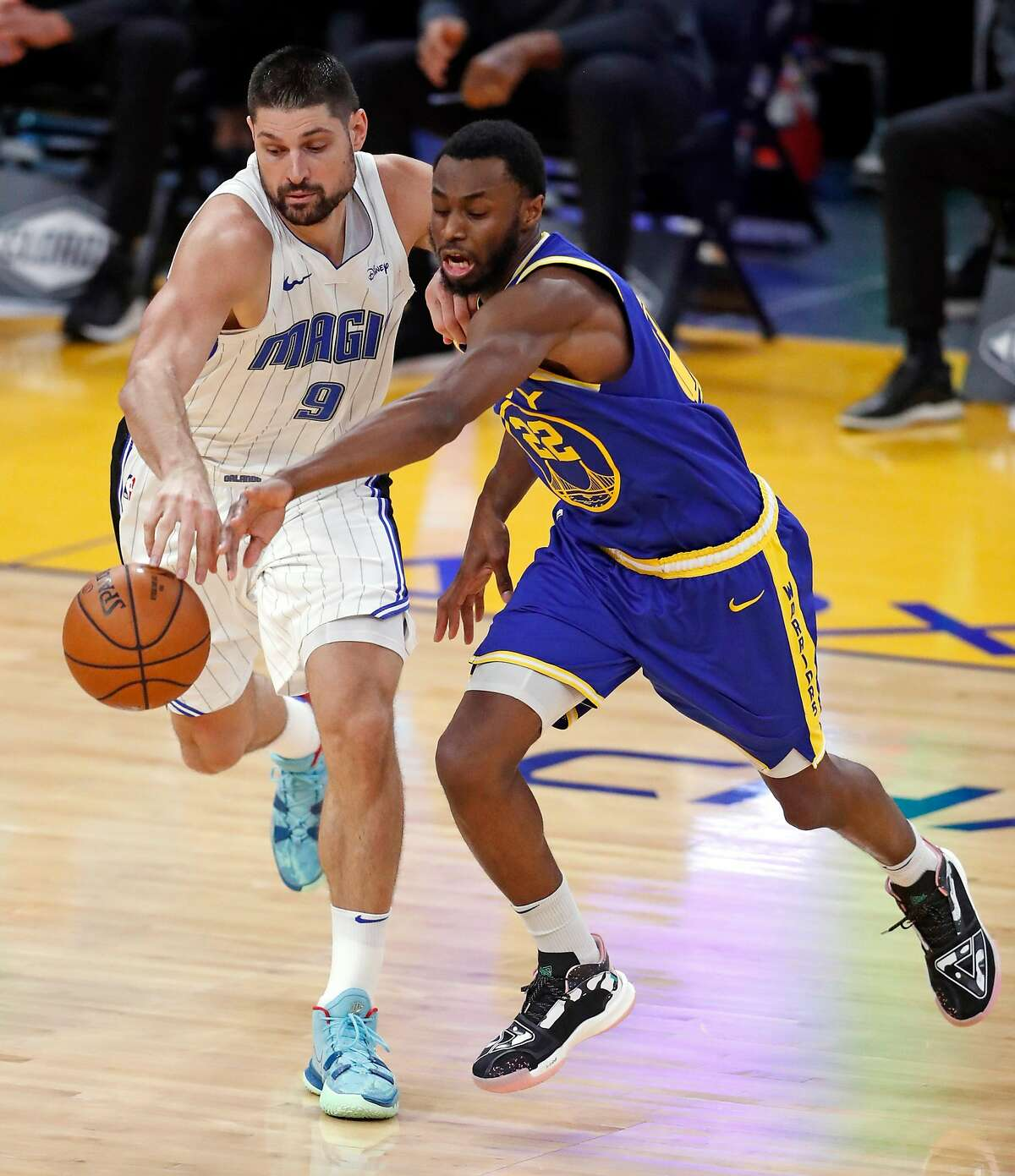 Golden State Warriors' Andrew Wiggins and Orlando Magic's Nikola Vucevic vie for loose ball in 2nd quarter during NBA game at Chase Center in San Francisco, Calif., on Thursday, February 11, 2021.