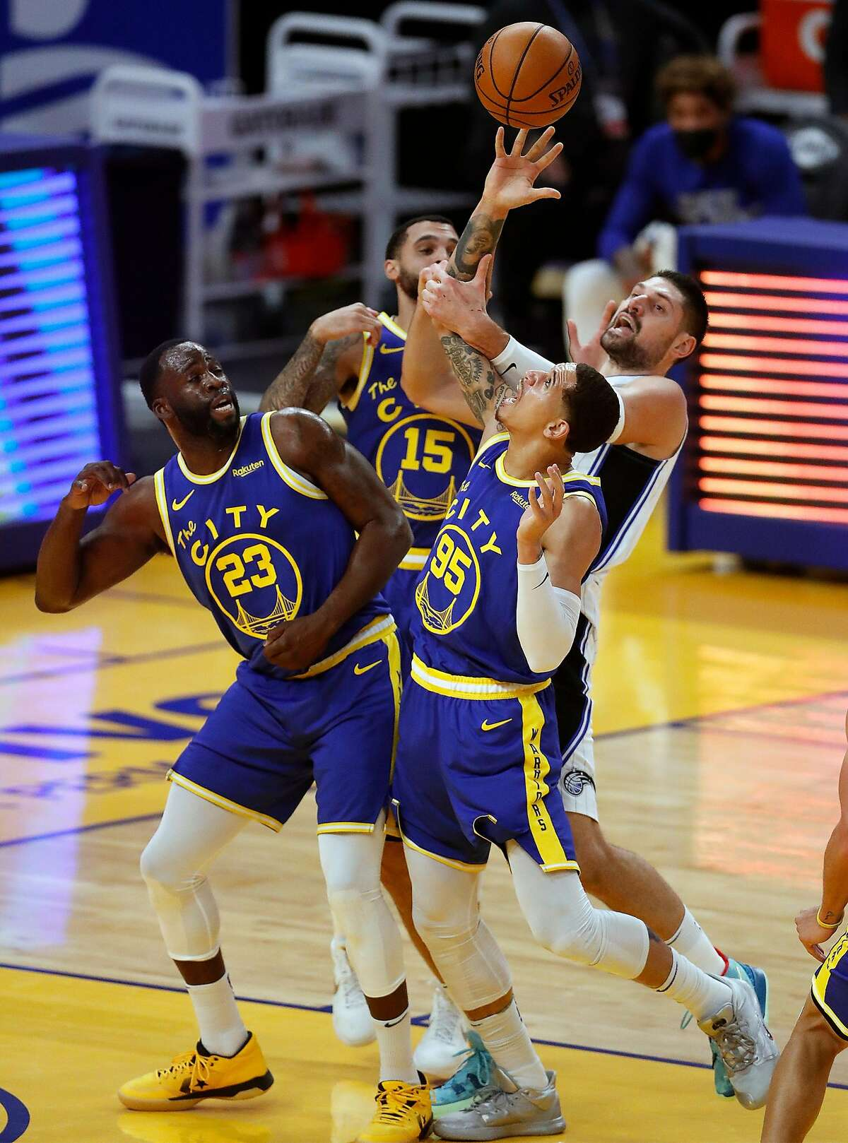 Golden State Warriors' Juan Toscano Anderson, Draymond Green and Mychal Mulder vie for rebound against Orlando Magic's Nikola Vucevic in 1st quarter during NBA game at Chase Center in San Francisco, Calif., on Thursday, February 11, 2021.
