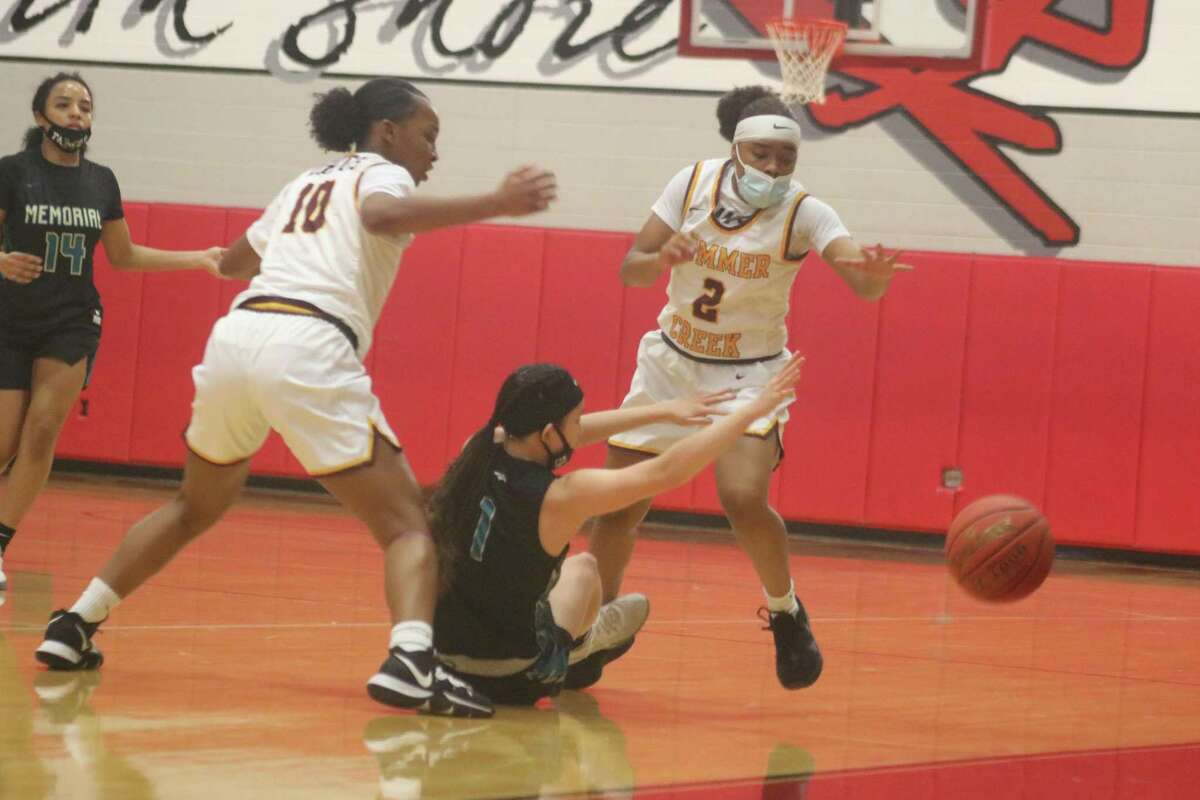 Pasadena Memorial's Madelyn DeLoSantos loses her balance and the ball as she was attempting to bring the ball up the floor against the Summer Creek defense of Tianna Rhodes (10) and Alayia Francis Thursday night.