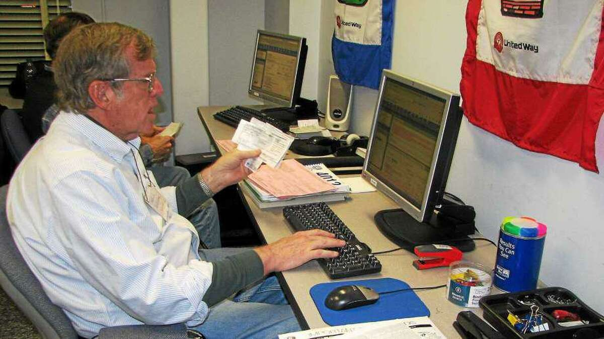 A volunteer assists a client with taxes at the VITA site at the Middlesex United Way office in Middletown.