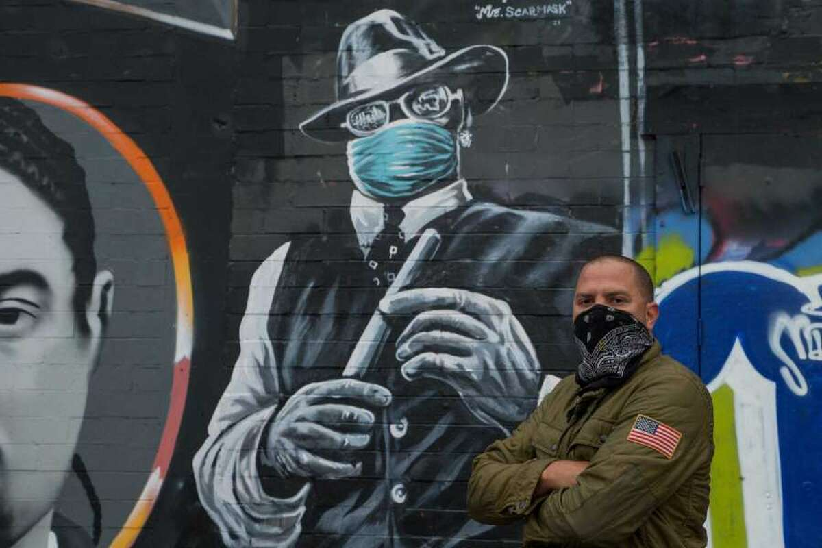 Kyle Holbrook poses for a photograph with his mural of Mr. Scarface on Wednesday, Feb. 11, 2021, in EaDo, Houston. Holbrook said he decided to have the legendary Houston rapper wearing a face mask as a reminder for Houstonians and visitors to wear masks.