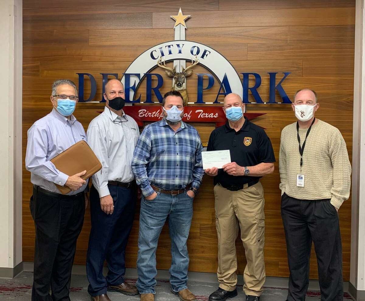 Deer Park Volunteer Fire Department chief Don Davis holds a check for $15,000 presented by Texas Molecular Deer Park Services LLC for the department's