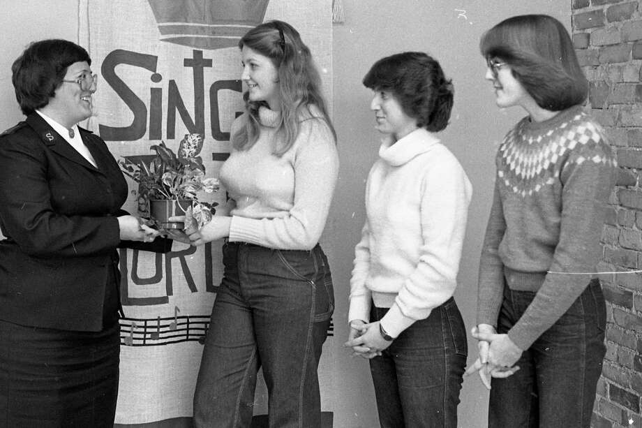 "(From left) Lt. Betty Grindle, of The Salvation Army, accepts a potted plant from Deanne Wall, vice president of administration for junior achievement; Mary Kubanek, president of junior achievement; and Lynne Doering, vice president of finance for junior achievement. Grindle was named ""Sweetheart of the Year"" by the Junior Achievement group for her outstanding contribution to the community. The photo was published in the News Advocate on this day in 1981. (Manistee County Historical Museum photo)"