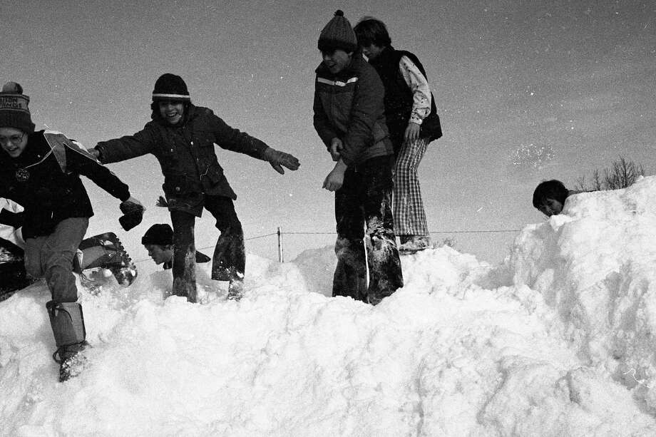 "Children in the city of Manistee play ""King on the Mountain"" after a snowstorm in early February 1981. (Manistee County Historical Museum photo)"