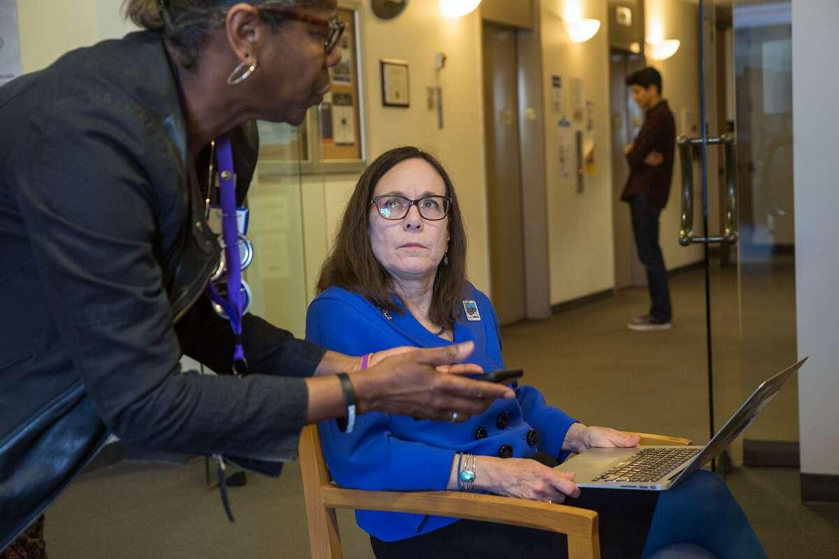 Susan Solomon (right), president of UESF, talks to SEIU Local 1021 field representative Kim-Shree Maufas at the San Francisco Unified School District building on March 12.