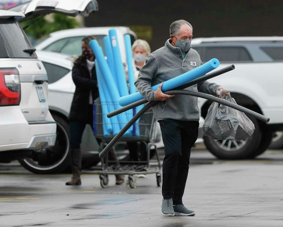 A man carries grey insulation tubing along with blue pool noodles after a rush on pipe insulation forced shoppers to consider alternative materials as temperatures plummet.
