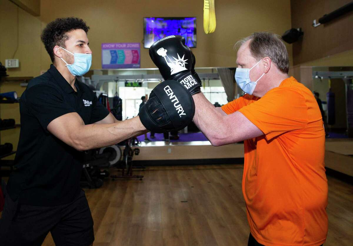 Anthony Purser, 65, works on Rock Steady Boxing, a workout designed to fight Parkinson's disease, with trainer Armin Smith, 33, Thursday, Feb. 4, 2021, at Anytime Fitness in League City. Purser, of Dickinson, learned he had Atrial Fibrillation (AFib), through his Apple Watch. Four days before Christmas, he underwent a minimally invasive heart surgery called atrial fibrillation ablation to correct the issue. Today, Purser is recovering well and has gone back to his normal workout sessions.