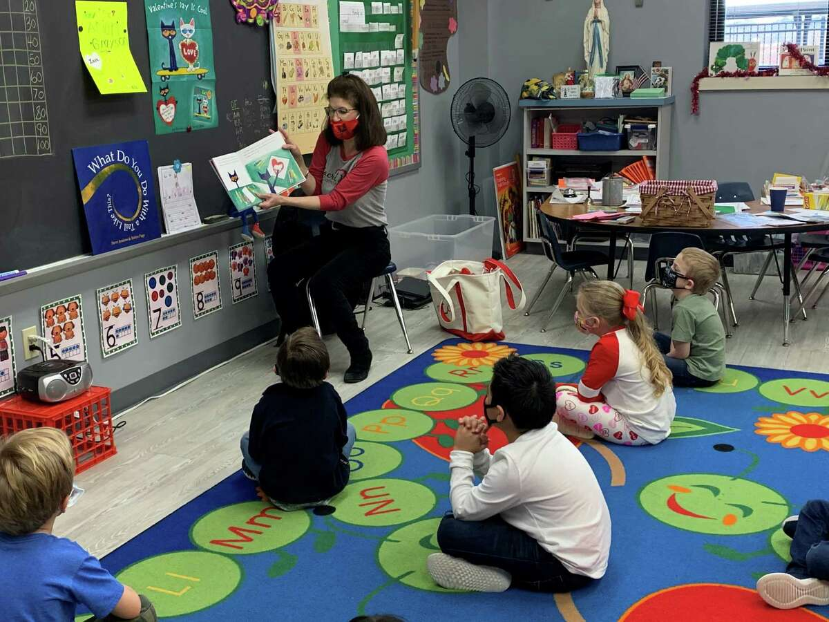 """Sacred Heart Catholic School enjoyed a """"teacher swap"""" during Catholic Schools Week and the teachers taught different grade levels for the morning. Mrs. Dianna Carroll, Middle School Language Arts, keeps the Pre-K students entertained by reading her favorite Pete the Cat story."""