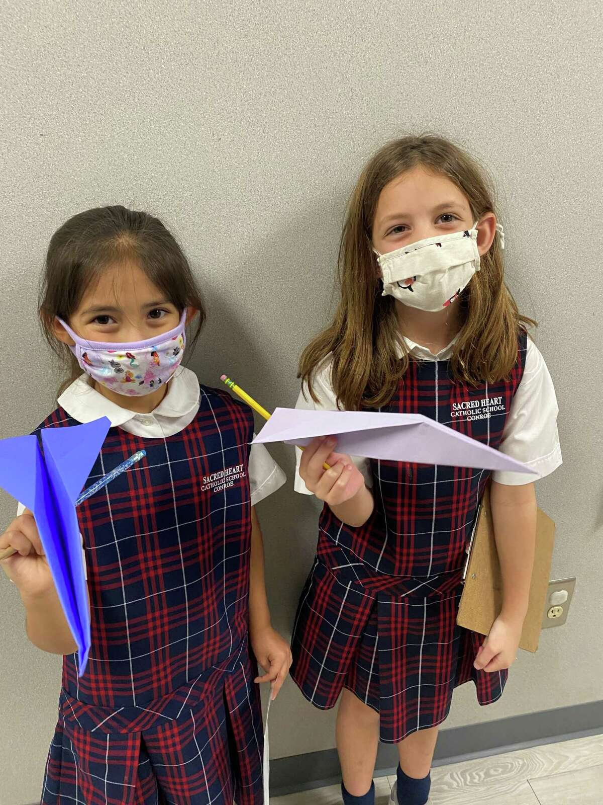 Second graders Ally Gonzales and Anna Beth Lee discover how to apply the scientific method during a S.T.R.E.A.M. (Science, Technology, Religion, Engineering, Art, and Math) activity with airplanes during Catholic Schools Week at Sacred Heart Catholic School.