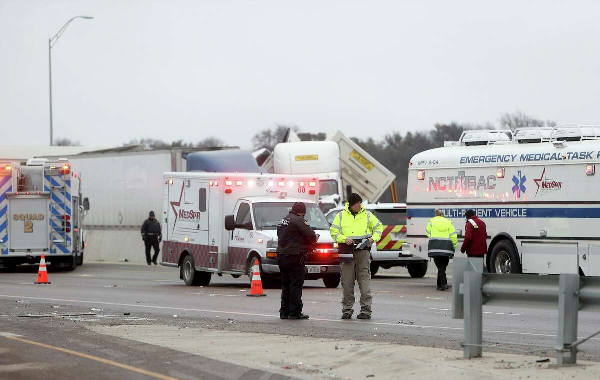 First responders work the scene of a fatal crash on I-35 near downtown Fort Worth on Thursday, Feb. 11, 2021. Police say at least five people were killed and dozens injured in a massive crash involving 75 to 100 vehicles on an icy Texas interstate. (Amanda McCoy /Star-Telegram via AP)