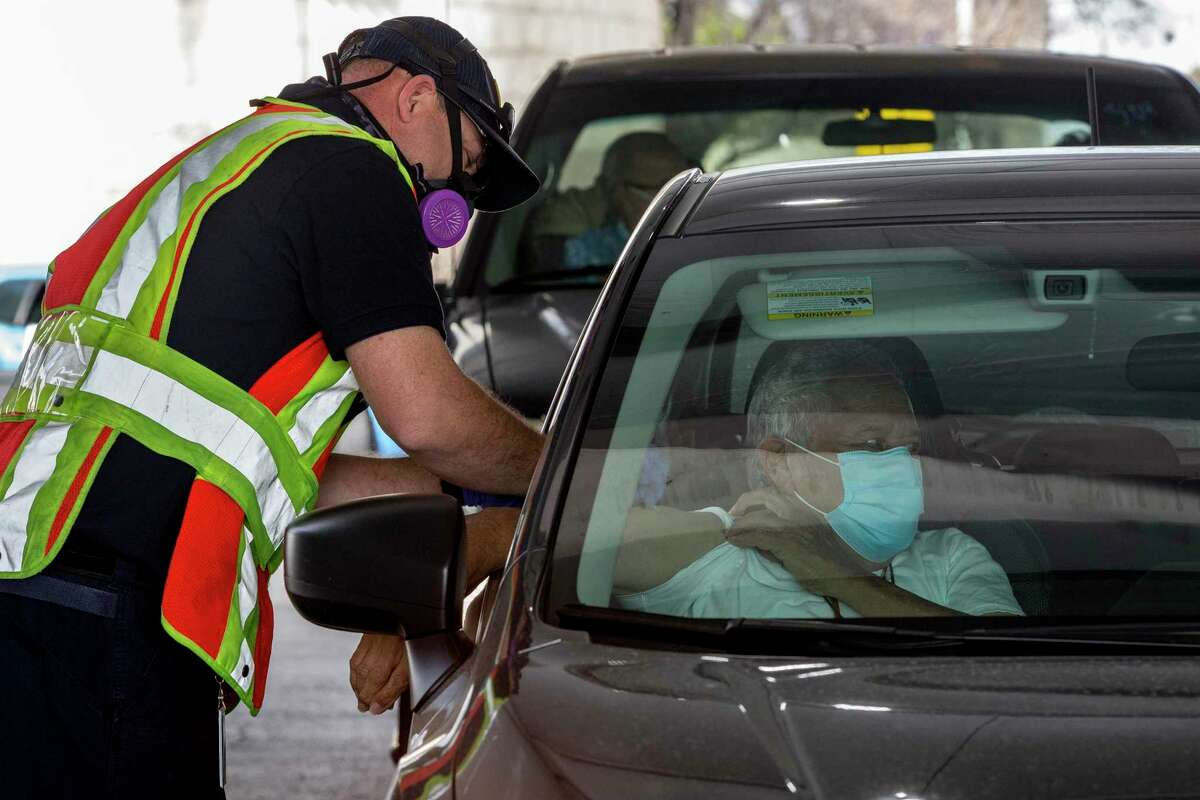Enrique Palacios is given his first dose of the Moderna vaccine by a member of the San Antonio Fire Department on Jan. 29, 2021. The fire department is in charge of the drive thru vaccination line at the Alamodome.