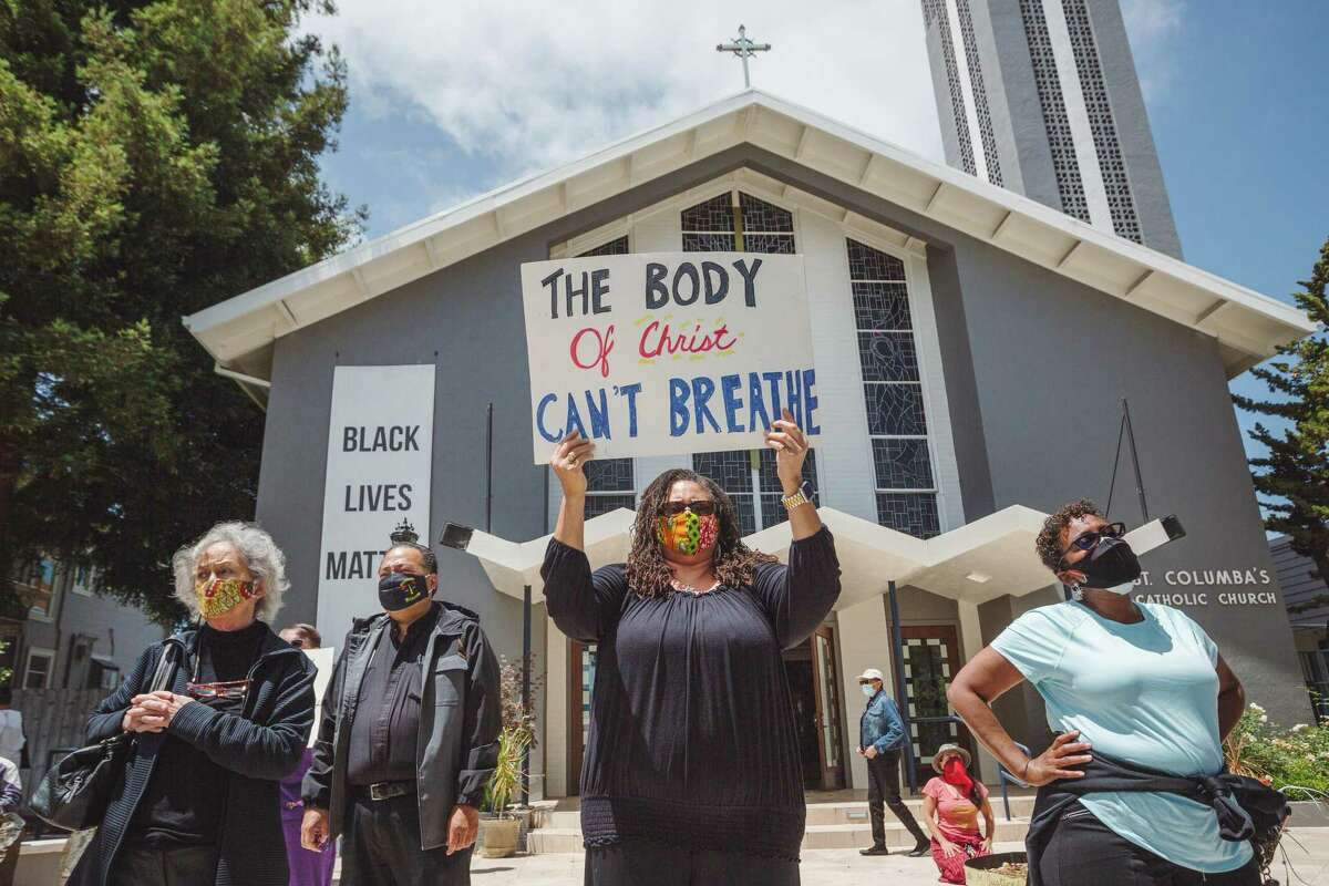 Parishoners participate in a Black Lives Matter protest outside of St. Columba Catholic Church in Oakland, Calif. on Sunday, June 28, 2020.