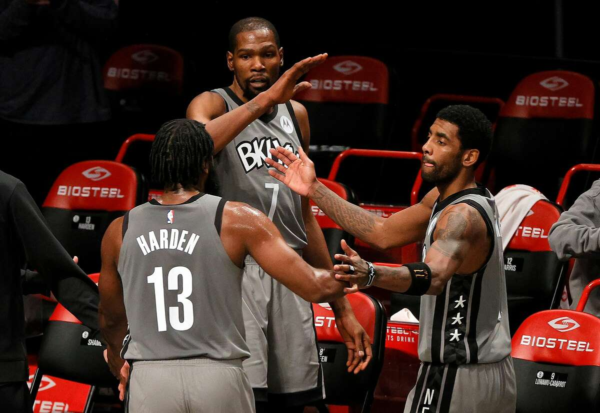 NEW YORK, NEW YORK - JANUARY 25: James Harden #13, Kevin Durant #7, and Kyrie Irving #11 of the Brooklyn Nets high-five after coming off the court during the second half against the Miami Heat at Barclays Center on January 25, 2021 in the Brooklyn borough of New York City. The Nets won 98-85. NOTE TO USER: User expressly acknowledges and agrees that, by downloading and or using this Photograph, user is consenting to the terms and conditions of the Getty Images License Agreement. (Photo by Sarah Stier/Getty Images)