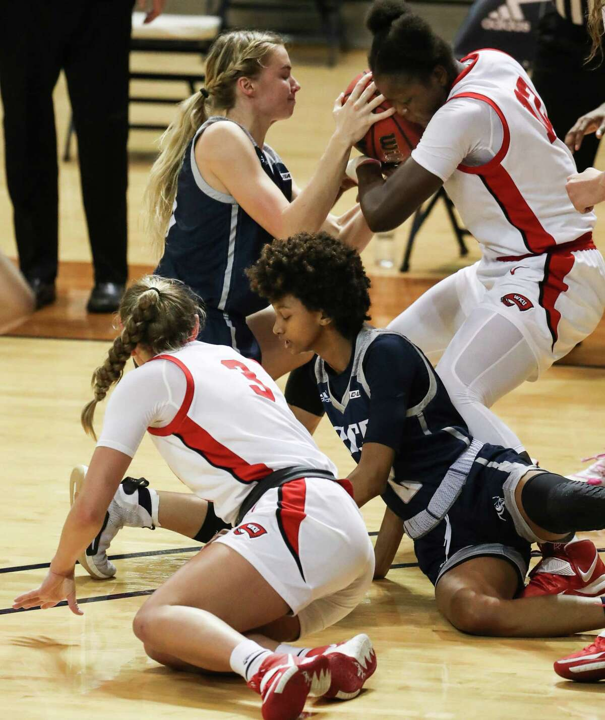 Rice guard Katelyn Crosthwait, top left and Western Kentucky's Fatou Pouye (12) fight for a looser ball over WKU's Ally Collett (3) and Rice's Sydne Wiggins (2) during the first half of an NCAA women's basketball game on Friday, Feb. 12, 2021, at Tudor Field House in Houston.
