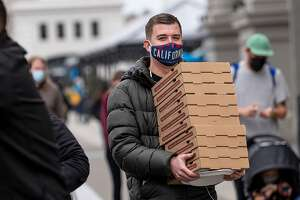 A person wearing a protective mask carries pizza boxes on The Embarcadero in San Francisco, California, U.S., on Thursday, Feb. 11, 2021. The U.S. Centers for Disease Control and Prevention Wednesday began recommending that Americans wear a cloth mask over a medical mask to slow the spread of Covid-19, along with other options to improve mask fit. Photographer: David Paul Morris/Bloomberg